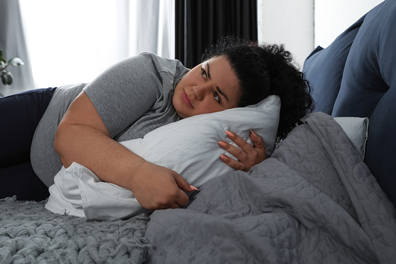 Overweight woman on bed