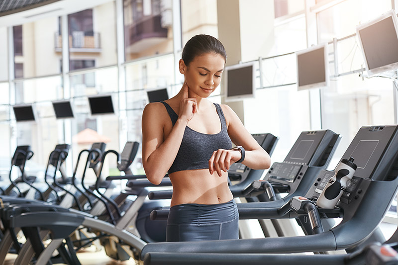 Woman on a treadmill checking pulse