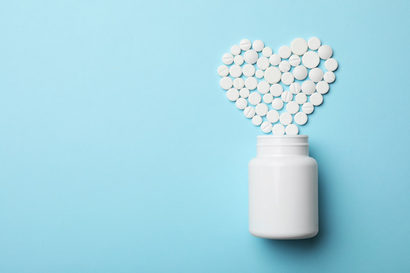 asprin pills in the shape of a heart on a blue background